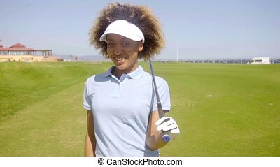Smiling friendly African American woman golfer