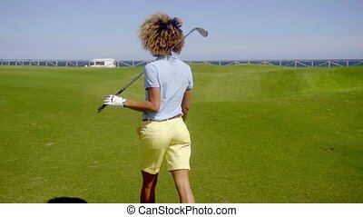 Female golfer walking down a fairway on a golf course away...