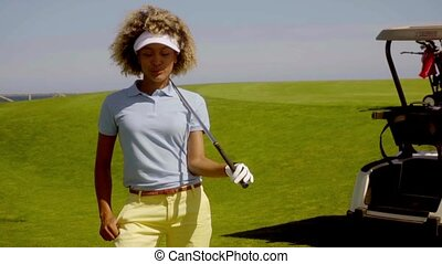 Young woman golfer watching her ball on the course