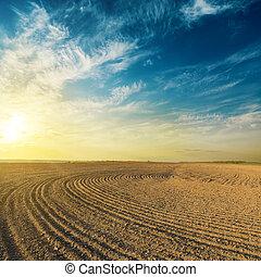 black plowed field in sunset