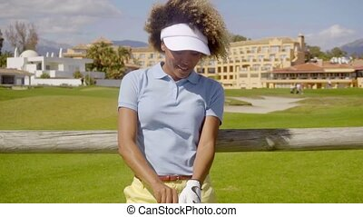 Young African American golfer on a coastal course standing...