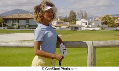 Attractive young woman golfer leaning on a fence -...