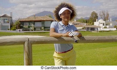 Attractive female golfer leaning on a wooden fence at the...