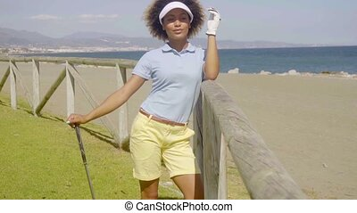 Attractive female golfer leaning on a wooden fence with a...