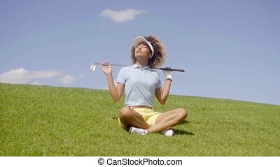Jaunty young woman golfer sitting on the green - Jaunty...