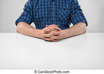 Cropped portrait of a man sitting with his clasped hands....