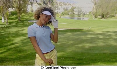 Smiling young woman golfer on a golf course posing for the...