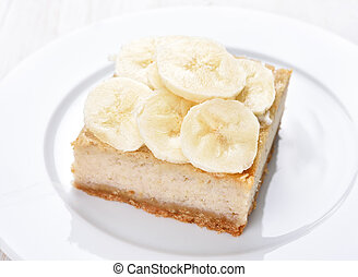 Banana cheese cake on white plate, close up view