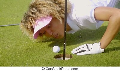 Young woman blowing her golf ball into the hole - Young...