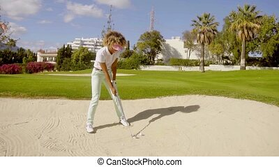 Young woman golfer playing out of a bunker - Young woman...