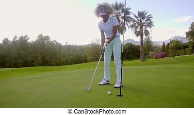 Attractive young woman playing a round of golf lining up her...