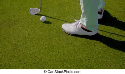 Woman golfer wearing golfing shoes standing on a golf course...