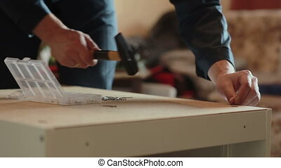 man assembles parts of furniture using a hammer.