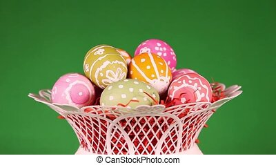 Rotating Easter eggs in basket in front of green background