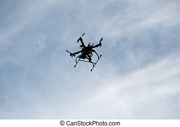flying drone with camera on the sky Silhouette of copter in...