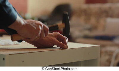 man assembles parts of furniture using a hammer. - male...