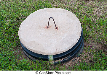 Septic tank lid in the middle of a yard. - Close up of...