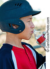 Teen baseball boy in dugout drinking water - American...