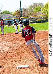 Teenage baseball boy running around first base - Teen...