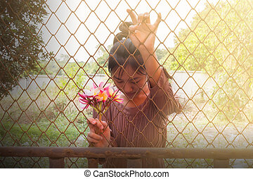 Women with flowers in hand behind iron bar