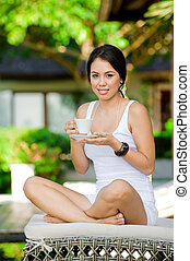 Relaxing Outdoors - An attractive young woman relaxing...