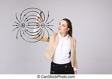 Young woman, physics teacher draws a diagram of the electric...