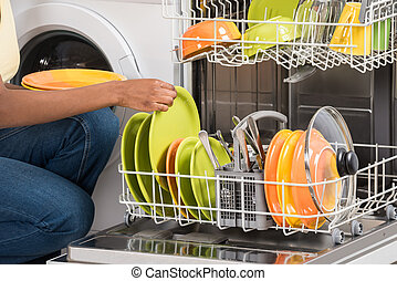 Woman Arranging Plates In Dishwasher - Close-up Of Woman's...