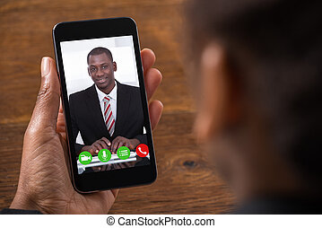 Businesswoman Videochatting On Mobile Phone - Close-up Of...