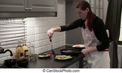 Woman puts shrimp on a plate - The woman in an apron in the...