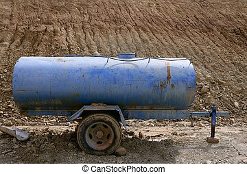 Blue water container trailer to wet soil in roads...