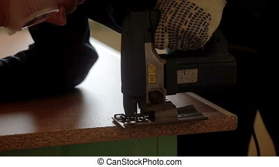 male worker using the jigsaw. Furniture assembly. - male...
