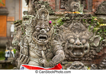 Traditional demon guard statue carved in stone on Bali...