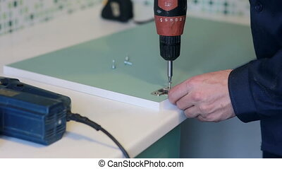 man assembles furniture using a power screwdriver - male...