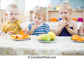 Three funny kids eating fruits in day care center