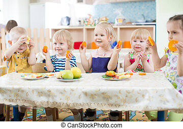 Funny kids eating fruits in kindergarten or day care centre...