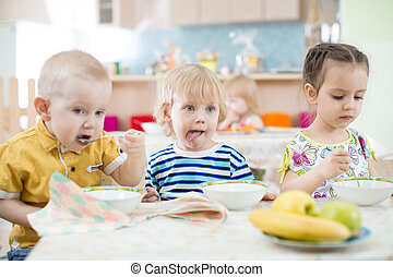 Funny little kids eating from plates in day care centre -...
