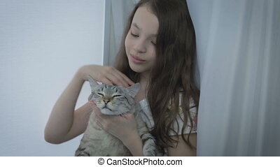 Beautiful little girl gently communicates with your loved cat at window.