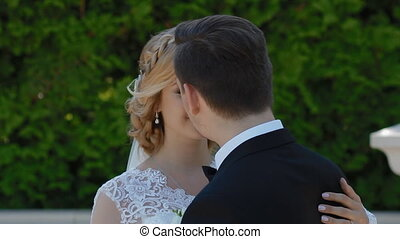 Bride and groom dance outdoor in sunny day. They whirl and...