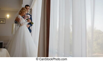 Happy bride and groom stand near the window Young caucasian...