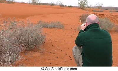 Man taking picture in desert - Rear view of bold man taking...