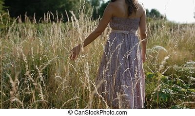Woman touch hight dry grass in the field - Young romantic...