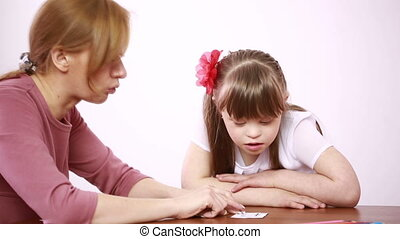 Downs Syndrome girl having speech therapy. learning disabled...