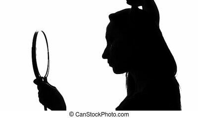 Woman combing her hair - Silhouette of a woman combing her...