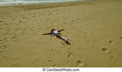 Young woman lying on her back on a beach with her arms...