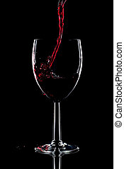 Red wine splash - Red wine being poured into a glass and...