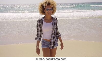Young woman walking on a windy sandy beach - Young woman...