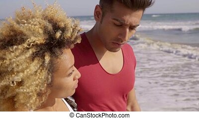 Loving young African American couple walking along a beach...