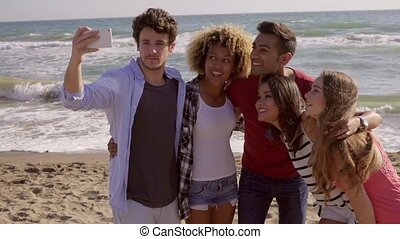 Funny Pictures On The Beach - Attractive young band take a...