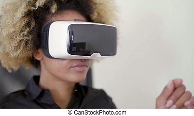 Businesswoman Working In Virtual Reality - Young mixed-race...