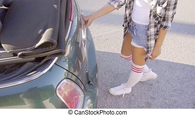 Girl taking out her roller skates from trunk - Young sexy...